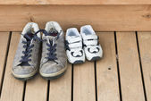 Big and small shoes on the back deck — Stock Photo