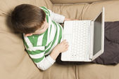 Top view of young boy using white Netbook computer — Stock Photo