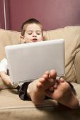 молодой мальчик работает на компьютере netbook — Стоковое фото