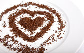 Heart of chocolate chips on a white plate porcelain — Stock Photo