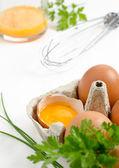 Vejce v kartonu a vaječného žloutku — Stock fotografie