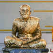 Golden statue of old Buddhist monk - Stock Photo