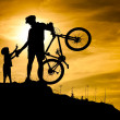 Stock Photo: Mountain biker silhouette with his son at top of hill.