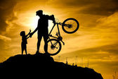 Mountain biker silhouette with his son at the top of the hill. — Stock Photo