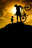 Mountain biker silhouette at dawn. Dad with son — Stock Photo