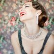Happy retro woman smiling looking to the side against grey floral background. Retro styled soft portrait — Stock Photo
