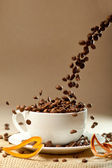 A cup of coffee to get energy and become vivacious on brown old paper background. focus on beans in a cup — Stock Photo