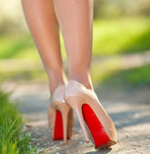 Slim female legs in high-heeled shoes outdoors. sunlight — Stock Photo