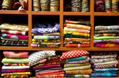 Multicolored scarfs on a shop counter, pile of colorful fabric — Stock Photo
