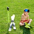 Portrait of attractive child sitting on grass with ski — Stock Photo