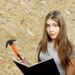 Stock Photo: Beautiful girl worker with hammer and manual book
