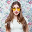 Cute summer woman wearing trendy yellow glasses over flower background — Stock Photo