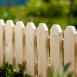 Detail of a wooden picket garden fence with green grass in the background. Daylight — Stock Photo
