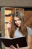 Beautiful girl worker with a hammer and a manual book — Stockfoto