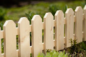 Detail of a wooden picket garden fence with green grass in the background. Daylight — Zdjęcie stockowe