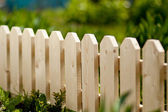 Detail of a wooden picket garden fence with green grass in the background. Daylight — Photo