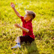 Boy sitting on green grass outdoor playing with soap bubbles — Stock Photo