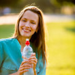 Portrait of young beautiful dark-haired woman wearing blue t-shirt drinking water at summer green park. backlit — Stock Photo