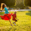 Carefree mother and child having fun in summer park, run and jump in motion. backlit — Stock Photo