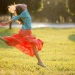 Young woman jumping in the park in motion. Soft back light — Stock Photo
