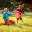 Mother and son having fun in the spring park in motion. backlit. focus on mother — Stock Photo