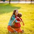 Carefree and happy family having fun outdoors in motion. backlit. focus on mother — Stock Photo