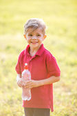 Happy boy with bottle of water on natural background on sunny summer day — Zdjęcie stockowe