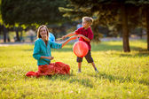 Mother and son having fun in the spring park in motion. backlit. focus on mother — Stok fotoğraf
