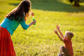 Happy family having fun outdoors in summer park. backlit. focus on mother — Stok fotoğraf