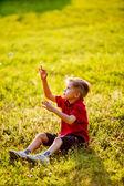 Niño sentado sobre la verde hierba jugando al aire libre con pompas de jabón — Foto de Stock