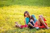 Carefree adorable mother and child having fun in summer park in motion. backlit. focus on mother — Stock Photo