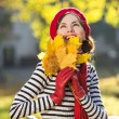 Happy fall woman smiling joyful and blissful holding autumn leaves outside in colorful fall forest on a sunny day. focus on hands with leaves — Stock Photo