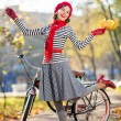 Stock Photo: Beautiful womwith bike in autumn park having fun. Hollywood style