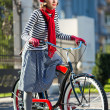 Stock Photo: Carefree womwith bicycle riding on street having fun and smiling