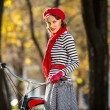 Style woman cycling on her bicycle in autumn park on a sunny day wearing red scarf, beret and gloves. Lifestyle — Stock Photo
