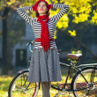 Young woman having fun in autumn park, standing with hands behind head and looking up to sky. retro city bike behind. — Stock Photo