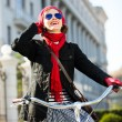 Carefree adorable young woman riding her city bike and looking to the sky. Urban scene — Stock Photo