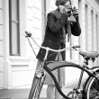Girl with retro camera and city bike. Urban life. black and white — Zdjęcie stockowe