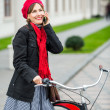 Urban biking. Young woman with bike is talking on the phone. Active People. Outdoors, lifestyle — Stock Photo