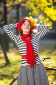 Portrait of beautiful happy woman with autumn leaves standing at the park. Retro fashion woman outdoors in autumn sunny day — Stock Photo