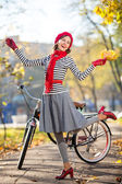 Beautiful woman with bike in autumn park having fun. Hollywood style — Stock Photo