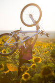 Young cyclist woman riding bicycle outdoors on a sunny day — Stock Photo