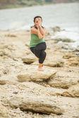 Pretty woman doing yoga near sea — Stock Photo