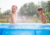 Family having fun in a pool — Stock Photo
