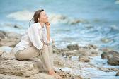Happy woman on vacation enjoying at rocky beach, woman meditating at the sea — Stock Photo