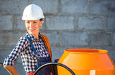 Pretty young woman builder and concrete mixer — Stock Photo