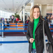 Young pretty woman with luggage at the international air — Stock Photo #39058601