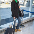 Young pretty woman with luggage at the international air — Stock Photo