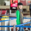 Young pretty woman with luggage at the international air — Stock Photo #39058633