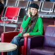 Stock Photo: Wompassenger at airport lounge with luggage talking to phone
